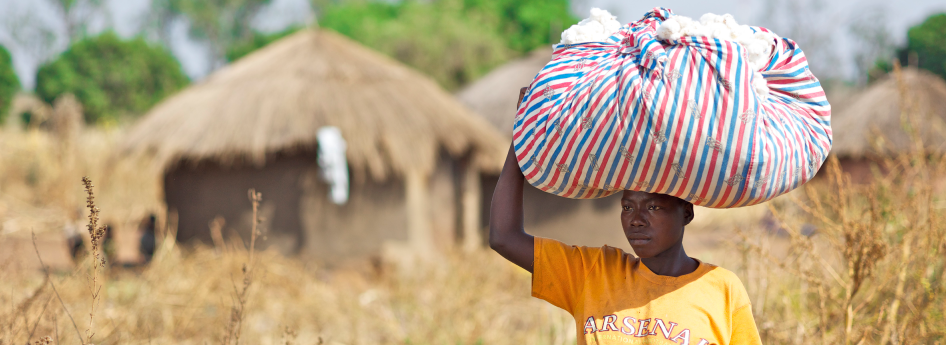 This young helper carries her harvest to the collection point. She transports the fluffy cotton fibres as women in Africa transport nearly everything: on her head.